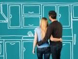 Happy embracing couple planning their home kitchen furnishing renovation.