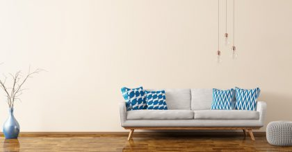 Modern interior of living room with white sofa, knitted pouf, vase and bulbs panorama 3d rendering